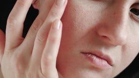 Plan rapproché d'un visage du ` s de femme La fille touche les doigts de la peau de problème avec les pores agrandis, l'examinant clips vidéos