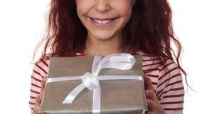 Plan rapproché d'un visage heureux de fille avec un cadeau de nouvelle année dans des mains banque de vidéos