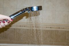 Plan rapproché d'un woman& x27 ; main de s vérifiant la température de l'eau dans la douche photos libres de droits