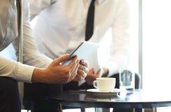 Plan rapproché d'une équipe moderne d'affaires utilisant la tablette à travailler avec des données financières images stock