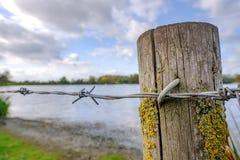 Plan rapproché d'une barrière de barbelé vue encadrer un lac à une réserve naturelle images stock