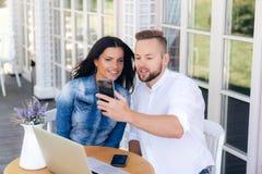 Plan rapproché d'une belle fille avec les cheveux foncés et d'un type élégant s'asseyant dans un café dehors, causant sur un appe image libre de droits