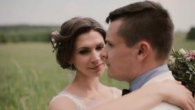 Plan rapproché d'une belle jeune mariée Elle étreint son marié et regarde tendrement in camera puis dans ses yeux Jour du mariage banque de vidéos