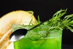 Plan rapproché d'une boisson d'estragon Un verre de freen le cocktail alcoolique avec une cuillère Boisson et melon de fines herb photos libres de droits