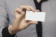 Plan rapproché d'une carte de visite professionnelle de visite vide dans une main du ` s de femme Photo libre de droits