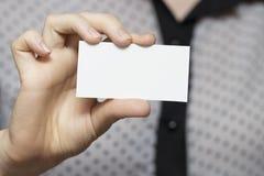 Plan rapproché d'une carte de visite professionnelle de visite vide dans une main du ` s de femme Images stock
