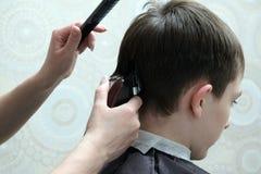Plan rapproché d'une coupe de cheveux masculine Les mains femelles d'un coiffeur avec un trimmer et un peigne noir, font une coif photographie stock
