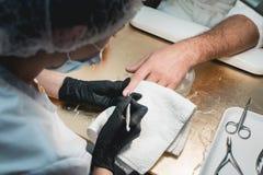 Plan rapproché d'une cuticle de Cleaning Off The de manucure des doigts du ` s de personne photo stock