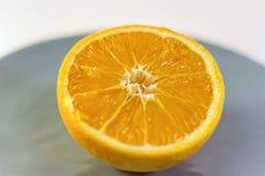 Plan rapproché d'une demi orange d'un plat bleu Image libre de droits