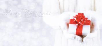 Plan rapproché d'une femme avec un présent dans des ses mains avec le joyeux Christ photos stock