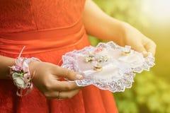 Plan rapproché d'une femme dans une robe rouge tenant des anneaux de mariage Photo libre de droits