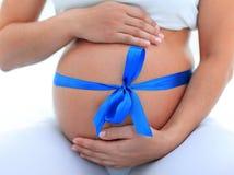 Plan rapproché d'une femme enceinte attachant un ruban bleu sur son ventre Photographie stock