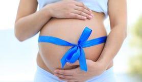 Plan rapproché d'une femme enceinte attachant un ruban bleu sur son ventre Photos libres de droits