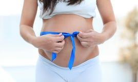 Plan rapproché d'une femme enceinte attachant un ruban bleu sur son ventre Images libres de droits