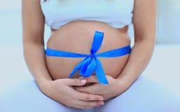 Plan rapproché d'une femme enceinte attachant un ruban bleu sur son ventre Photo stock