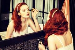 Plan rapproché d'une femme rousse appliquant le mascara dans le miroir photographie stock libre de droits