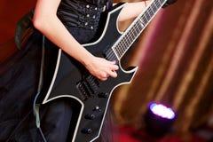Plan rapproché d'une femme sur l'étape jouant sur l'électro guitare La fille rockstar dans une robe noire Images stock