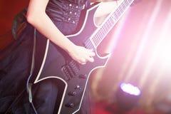 Plan rapproché d'une femme sur l'étape jouant sur l'électro guitare La fille rockstar dans une robe noire Photographie stock libre de droits