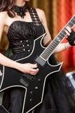 Plan rapproché d'une femme sur l'étape jouant sur l'électro guitare La fille rockstar dans une robe noire Photo stock