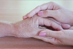 Plan rapproché d'une femme tenant une main du ` s de femme agée Image libre de droits