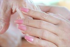 Plan rapproché d'une femme tenant une main du ` s de femme agée Photos stock