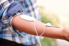 Plan rapproché d'une femme tenant une machine d'électrode dans sa main et avec des électrodes d'electrostimulator dans le bras da Images libres de droits