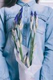 Plan rapproché d'une fille dans une chemise de denim tenant un bouquet d'unblown Images libres de droits