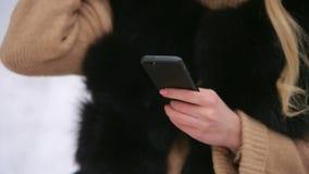 Plan rapproché d'une fille tenant un téléphone pendant l'hiver banque de vidéos