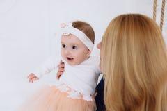 Plan rapproché d'une fille d'un an sur un fond clair riant et souriant L'enfant a l'amusement avec sa mère a photo stock