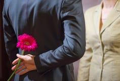 Plan rapproché d'une fleur de dissimulation d'homme derrière des femmes Photos libres de droits