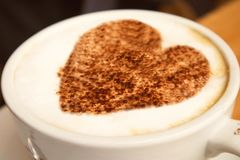 Plan rapproché d'une grande tasse blanche de cappuccino chaud de café avec le coeur de conception d'art là-dessus se tenant sur u Photos stock