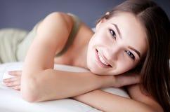 Plan rapproché d'une jeune femme de sourire se trouvant sur le divan photo stock