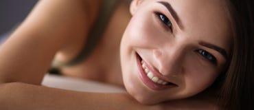 Plan rapproché d'une jeune femme de sourire se trouvant sur le divan images stock