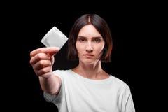 Plan rapproché d'une jeune femme sérieuse montrant un préservatif emballé sur un fond noir Concept sain de style de vie Copiez l' Image stock