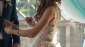 Plan rapproché d'une jeune mariée mettant un anneau de mariage d'or sur le doigt du ` s de marié Anneaux de mariage et mains des  Photo stock
