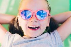 Plan rapproché d'une jeune petite fille heureuse se situant dans l'hamac et le regard Photo stock