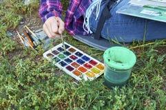 Plan rapproché d'une main de l'adolescence du ` s de fille prenant une peinture par le pinceau de l'ensemble de peintures d'aquar Image libre de droits