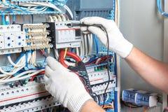 Plan rapproché d'une main du ` s d'électricien avec un outil de diagnostic dans son h photo libre de droits