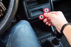Plan rapproché d'une main du ` s d'homme jouant avec un fileur tandis que dans un embouteillage sur le fond de l'intérieur du ` s Photographie stock libre de droits