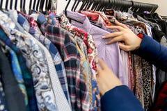Plan rapproché d'une main du ` s de femme dans une veste bleue, qui choisit dans des vêtements de boutique La femme achète des vê Image stock