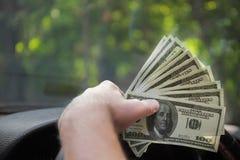 Plan rapproché d'une main du ` s d'homme avec l'argent Un homme d'affaires riche conduisant une nouvelle voiture sur un fond brou Photos libres de droits
