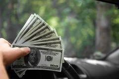Plan rapproché d'une main du ` s d'homme avec l'argent Un homme d'affaires riche conduisant une nouvelle voiture sur un fond brou Photos stock