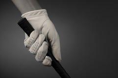 Plan rapproché d'une main enfilée de gants de golfeurs sur le club photographie stock