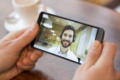 Plan rapproché d'une main masculine tenant un téléphone intelligent pendant un vide de skype photo libre de droits