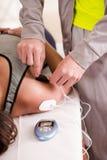 Plan rapproché d'une main personnelle d'entraîneur mettant des électrodes d'un electrostimulator dans l'épaule d'un deportist fem Photographie stock libre de droits