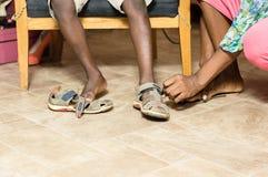 Plan rapproché d'une main portant une chaussure à un enfant photos libres de droits
