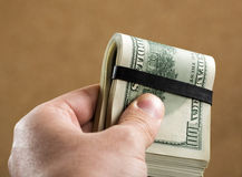 Main tenant $100 billets de banque Image stock
