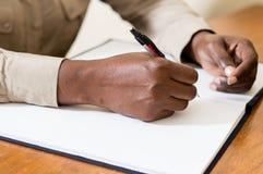 Plan rapproché d'une main tenant un stylo avec un carnet Images stock