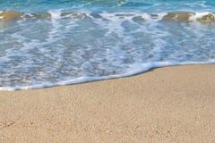 Plan rapproché d'une mousse de mer blanche sur un sable côtier jaune un jour ensoleillé L'espace marin de fond et de copie photographie stock