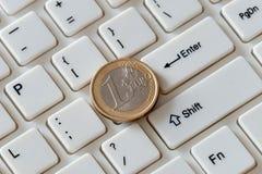 Plan rapproch? d'une pi?ce d'or en valeur un euro sur le clavier Commerce sur l'Internet S?quence type latine Fond photos stock